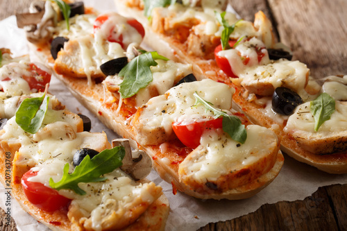 Homemade sandwich pizza baguette baked with chicken, cheese, tomatoes, olives and mushrooms close-up. horizontal