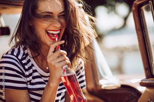 Kobieta w samochodzie cieszy się pijący koli Fototapeta
