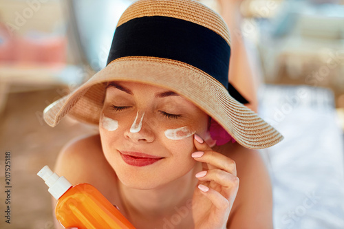 Young woman with sun cream on face holding sunscren bottle on the beach. Female in hat applying  moisturizing lotion on skin.