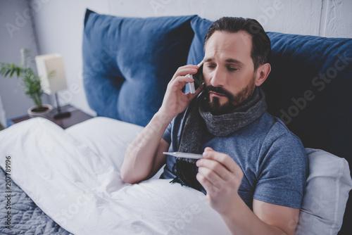 Fotografia sick man holding thermometer