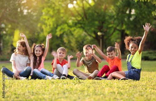 Cute little children sitting on grass outdoors on sunny day