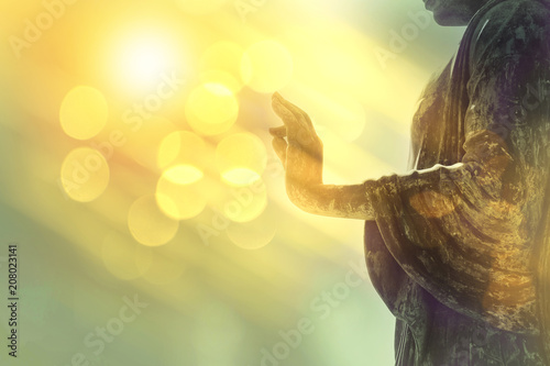 Leinwand Poster hand of buddha statue with yellow bokeh background, light of wisdom and concentr