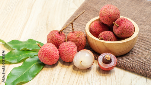Red lychee fruit on a wooden table.