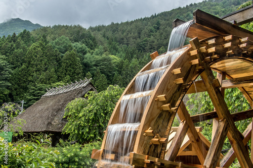 Fotografia The mill wheel rotates under a stream of water, background of  village with trad