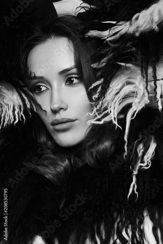 Portrait of young beautiful brunette woman wearing elegant faux fur coat with long black and white hair. Gorgeous sexy caucasian female model with evening makeup posing with raised crossed arms.