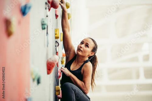 Wallpaper Mural Cropped view of fit business woman, climbing on atrificial rock in fitness, reaching new heights in business and sport