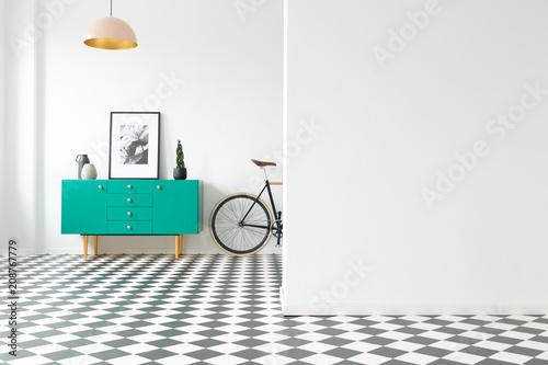 Fotografering Empty wall and turquoise cabinet with decorations standing next to a bike in a hallway interior with checkered floor