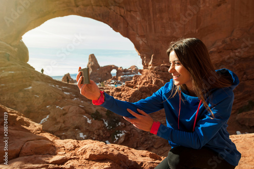 Fotografía Female traveller taikng self portraits with rock formation in the Arches Nationa
