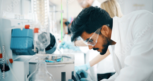 Fotografiet Male student of chemistry working in laboratory