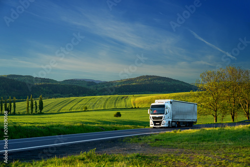 Wallpaper Mural White truck driving on the asphalt road in a rural landscape with forested mount