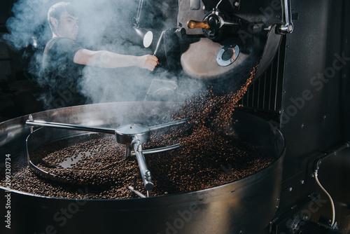Professional male roaster loading machine with coffee beans Fototapeta