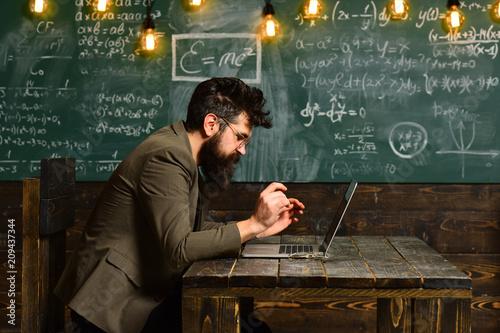 Canvas Print Bearded man work on laptop in classroom