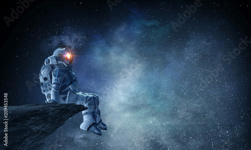 Leinwand Poster Spaceman on rock edge. Mixed media