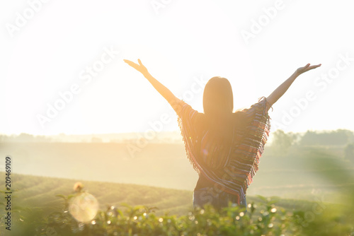 Lifestyle traveler women happy feeling good relax and freedom facing on the natural tea farm in the sunrise morning, Thailand. Travel Concept
