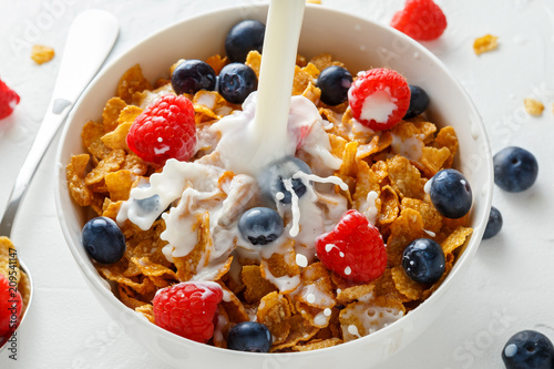 Canvas Print Healthy Morning Breakfast honey Corn flakes with fresh fruits of Raspberry, blueberries and pouring milk in bowl