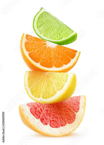 Isolated citrus slices. Pieces of grapefruit, orange, lemon and lime fruits on top of each other isolated on white background with clipping path