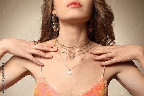 Photo Beautiful young woman with elegant jewelry on color background