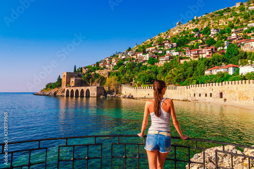 Photo Young woman look on ancient shipyard from Kizil Kule tower in Alanya peninsula, Antalya district, Turkey, Asia