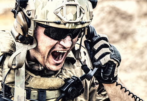Foto Special forces soldier, military communications operator or maintainer in helmet and glasses, screaming in radio during battle in desert