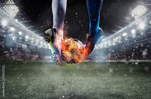 Obraz na płótnie Soccer players with soccerball on fire at the stadium during the match