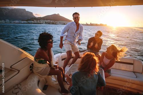 Billede på lærred Group of young people dancing in boat party