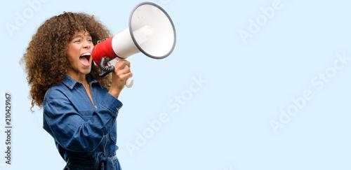 Vászonkép African american woman wearing blue jumpsuit communicates shouting loud holding