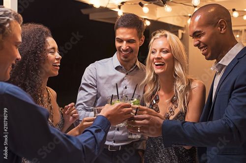 Friends toasting cocktail at night party