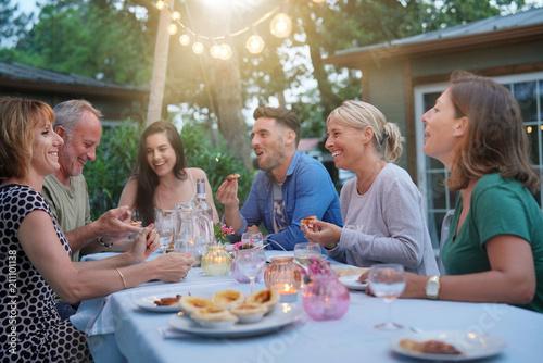Fotografia Friends enjoying summer barbecue dinner in garden