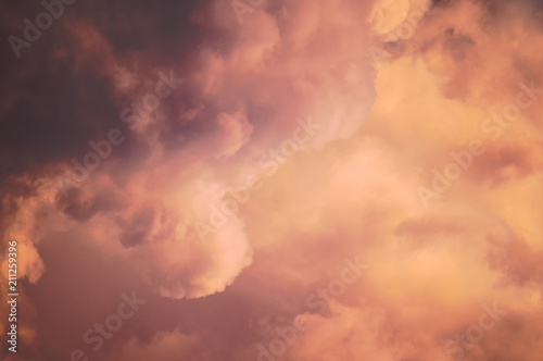 Blue sunset sky with texture of rare beautiful evening cumulus clouds in light of setting sun for designer's background. Pink vanilla heaven.