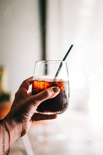 Foto Woman's hand holding glass of black cold brew coffee with ice