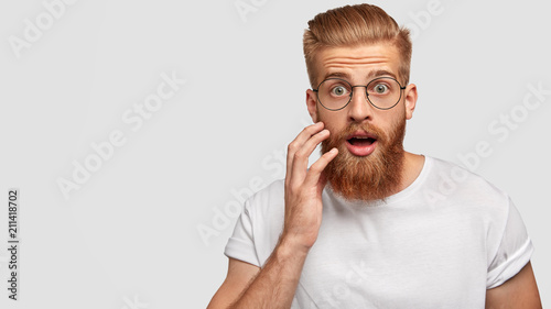 Leinwand Poster Astonished attractive male has ginger long beard, wonders sudden news, keeps mou