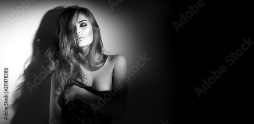 Sexy young woman black and white portrait. Seductive young woman with long hair posing in spotlight. Wide angle