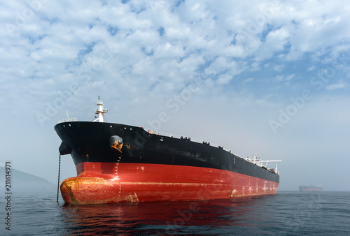 Supertanker is anchored in the roadstead on a foggy day.