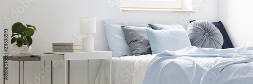 Fényképezés Real photo of a bed with blue bedding and cushions standing next to white tables