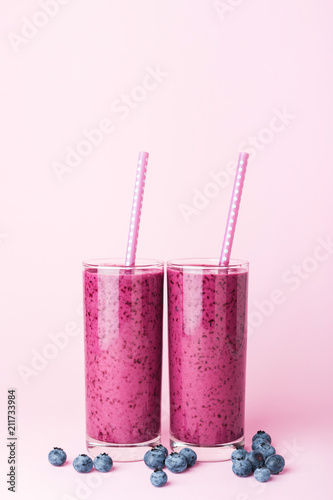 Canvas Print Two glasses of blueberries smoothie with straws on pink background