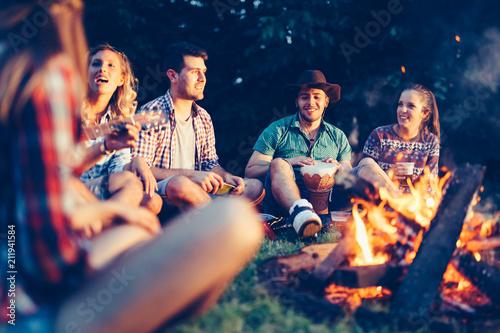 Leinwand Poster Friends enjoying music near campfire
