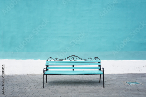 Blue bench on a background of blue wall. Front view, empty space. Fototapet