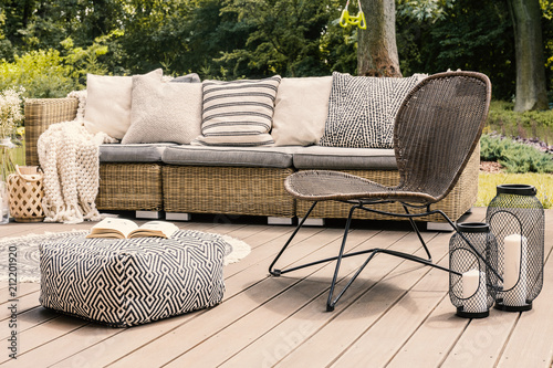 Fotografía Patterned pouf and rattan chair on wooden patio with pillows on sofa and lanterns