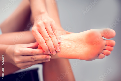 Tablou Canvas Woman hand holding foot with pain, health care and medical concept