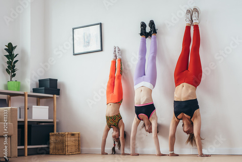 Females doing handstand pose near wall Fototapet