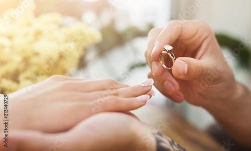 Man putting on girl finger engagement ring