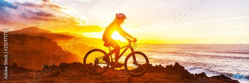 Slika na platnu Mountain biking cyclist riding bike on coast trail against sunset