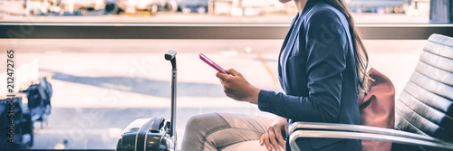 Plane passenger woman waiting for flight departure texting sms message on mobile phone at lounge airport. Businesspeople travel lifestyle panoramic banner.