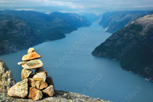 Leinwand Poster Stone cairn over Lysefjord and Preikestolen rock, Norway