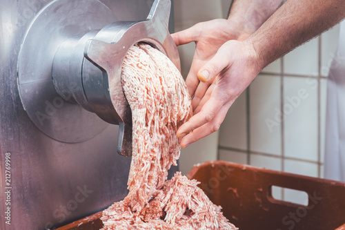 Minced meat flowing out of grinder in butchery Fototapet