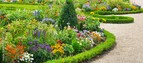 Valokuva Lush flower beds in the summer garden.Wide photo.