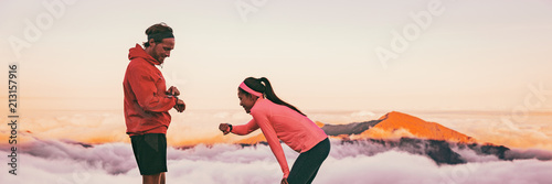 Runners tired breathing after training looking at their wearable tech sports watch checking heart rate health data. Two athletes couple running together in outdoors mountain banner panorama.