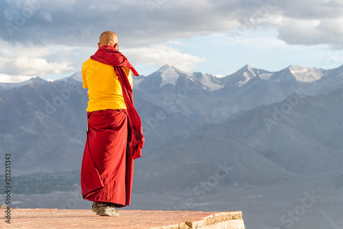 Tibetan monk Lama or Buddhist priest in red and yellow clothing standing in front of mountains with evening light.