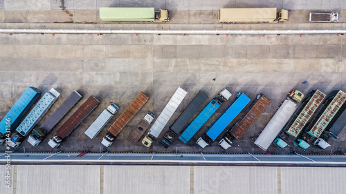 Photo Aerial top view of truck and cargo trailer unloading in logostics center