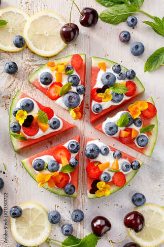 Watermelon pizza with addition of fersh blueberries, strawberries, natural yogurt and edible flowers, Delicious and healthy summer dessert